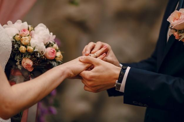 groom-mettendo-anello-al-dito-della-sposa_1157-338