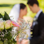 Close-up of bouquet with blurred newlywed couple in background at the park